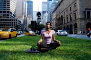To fit exercise into a hectic schedule, be creative. A patch of grass and a lunch break are all this New York businesswoman needs to strike a yoga pose . (Photo: Michael Goldman/Getty Images)